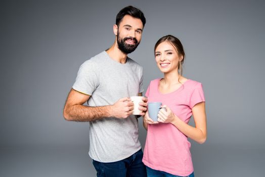 Smiling couple holding cups and looking at camera on grey