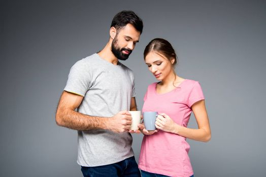 Smiling couple holding cups on grey