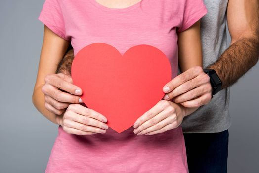 Partial view of young couple posing with red paper heart