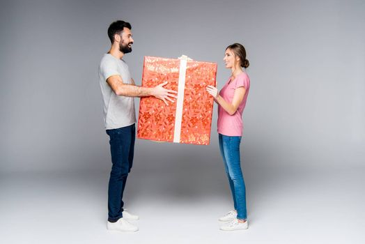 Young couple standing with big red gift box on grey