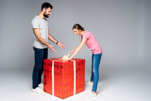 Young couple with big red gift box, woman opening present on grey