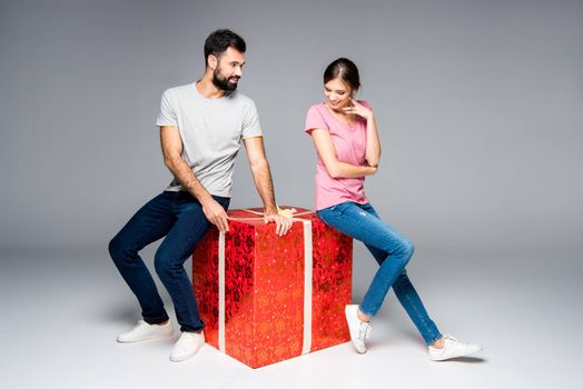 Young smiling couple sitting on big red gift box on grey