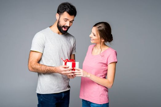 Happy couple standing with gift box on grey