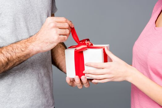 Partial view of happy couple standing with gift box on grey