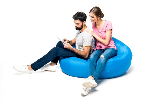 Young couple sitting on big blue pouf and using digital tablet, on white