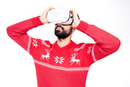 Young man using virtual reality headset on white