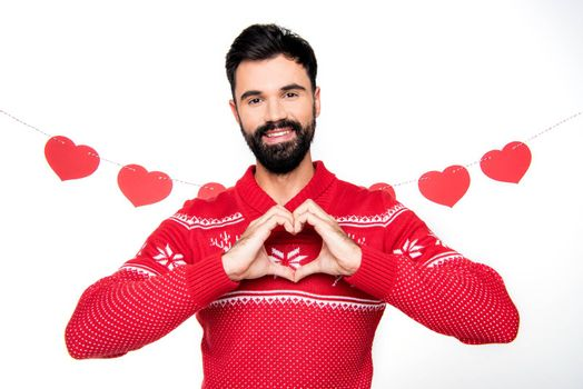 Cheerful man in red knitted sweater gesturing and looking at camera