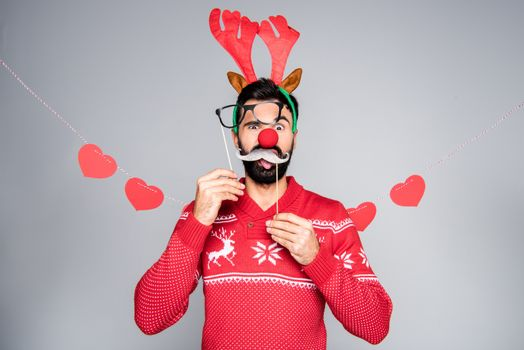 Bearded man in reindeer antlers headband holding party sticks and looking at camera