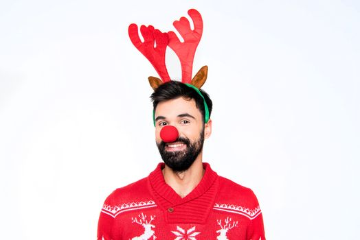 Smiling man in deer antlers and red nose looking at camera