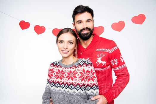 Smiling couple in knitted sweaters looking at camera on white