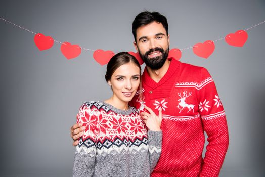 Smiling couple in knitted sweaters looking at camera on grey