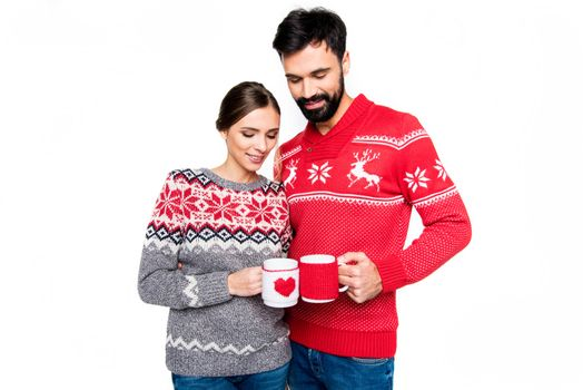Couple in knitted sweaters holding cups with hot drinks isolated on white
