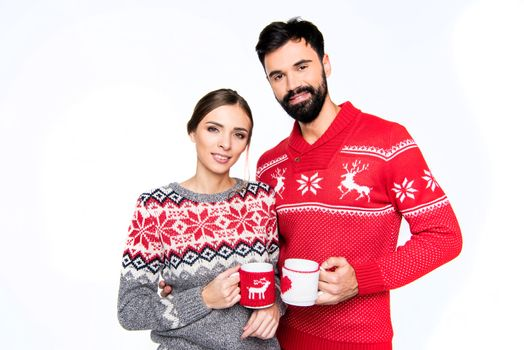Couple in knitted sweaters holding cups with hot drinks and looking at camera