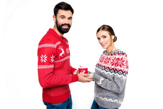 Couple in knitted sweaters holding cup with hot drink and looking at camera