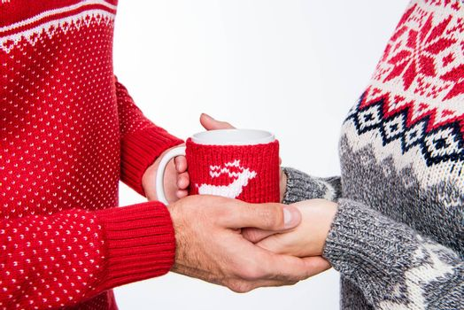 Partial view of couple in knitted sweaters holding cup with hot drink