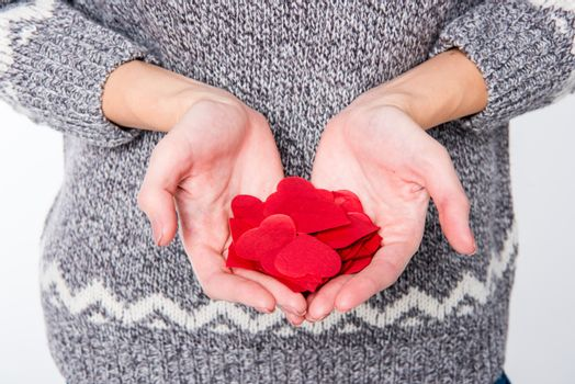 Female hands with pile of red paper hearts