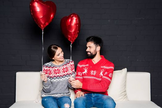 Couple with red hearts balloons sitting together on white couch