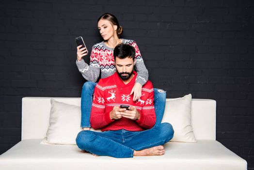 Young couple sitting on white couch and using smartphones
