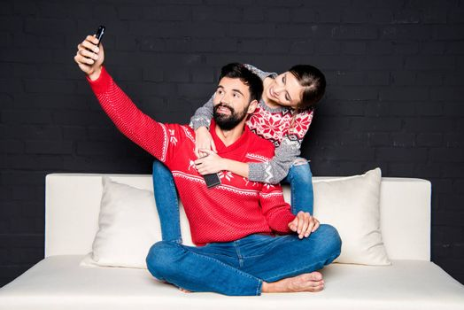 Young couple sitting on couch and taking selfie