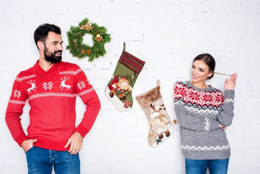 Flirting couple leaning on white wall with Christmas decorations