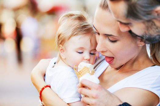 A baby boy is being hugged by his mother and father while fed with ice cream.
