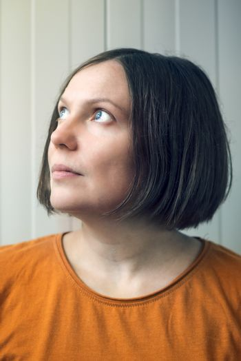 Hopeful woman looking up to sunlight from window