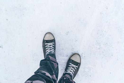 Top view of worn gray sneakers on white asphalt road