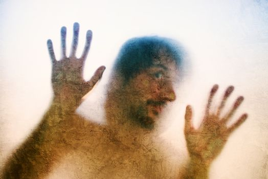 Trapped man, back lit silhouette of hands behind matte glass