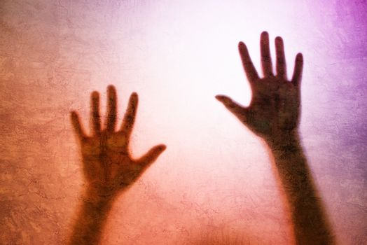Captured person, back lit silhouette of hands behind matte glass