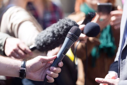 Reporters holding microphones conducting media interview