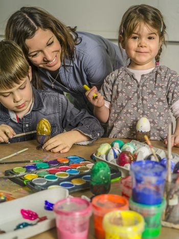 Photo of a mother and her children painting and decorating hard-boiled eggs for easter.