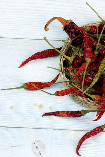 Arrangement of Dried Chili Peppers Full Body with Stems in Wicker Bowl closeup on Blue Wooden background. Top View