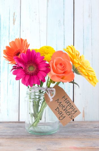 Bunch of flowers with happy mothers day gift label on wooden background