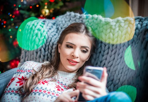 Beautiful smiling woman lying on grey couch and using smartphone