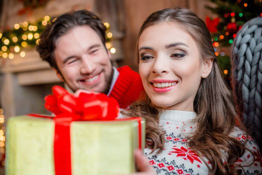 Close-up portrait of happy couple with christmas present