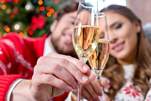 Close-up view of happy couple toasting with champagne glasses at christmastime