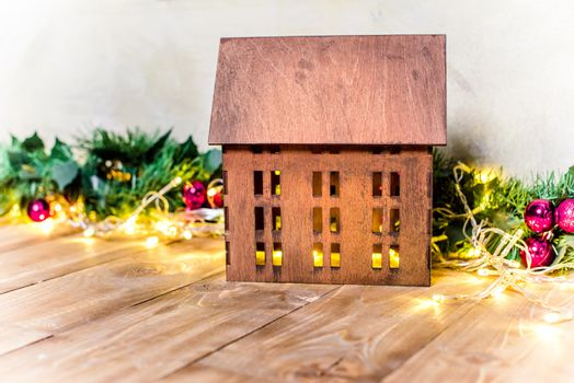 Close-up view of wooden house model and christmas decorations on floor