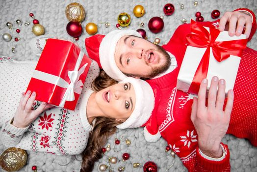Happy couple in santa hats lying on floor with gift boxes