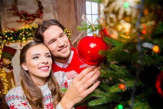 Happy young couple decorating christmas tree