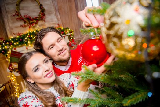 Happy young couple decorating christmas tree with shiny red bauble