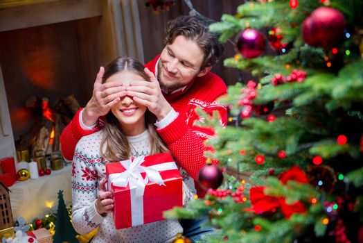 Happy couple with christmas present  sitting near fireplace