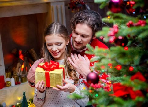Happy couple with christmas present  sitting and hugging near fireplace