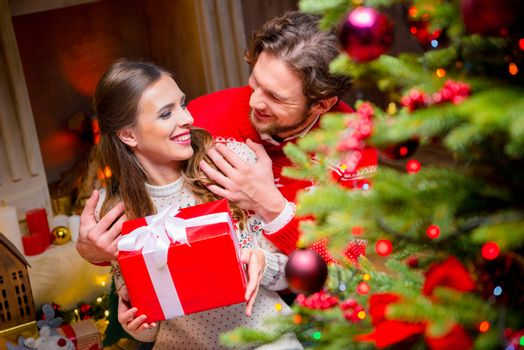 Happy couple with christmas present sitting on floor and hugging near fireplace