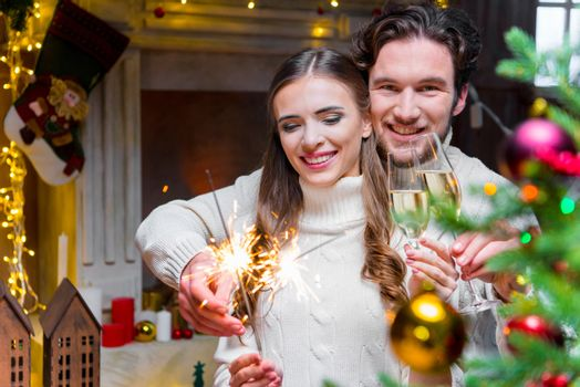 Young couple holding sparklers and glasses of champagne