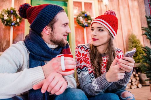 Young couple in warm clothes using a smartphone and drinking tea