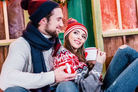 Loving couple in warm clothes holding cups of tea