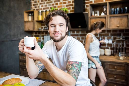 Smiling man in white t-shirt drinking coffee in kitchen and looking at camera