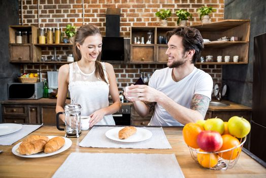 Smiling young couple drinking coffee at breakfast in kitchen