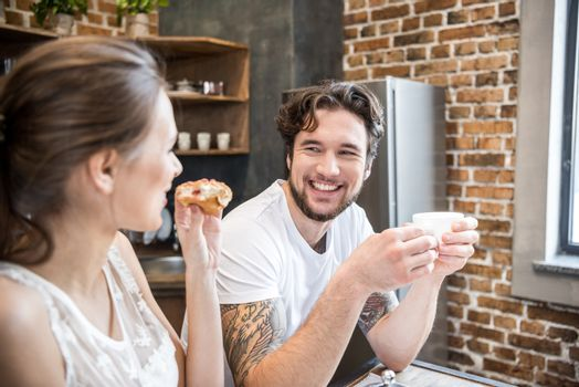 Happy young couple having breakfast and looking at each other in kitchen