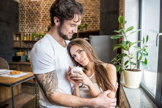 Smiling young man hugging beautiful young woman with coffee cup near kitchen window